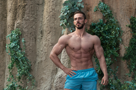 flexing: Young Man Standing And Flexing Muscles