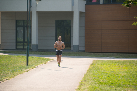 Young Bodybuilder Running In Park Area - Training And Exercising For Trail Run Marathon Endurance - Fitness Healthy Lifestyle Concept photo