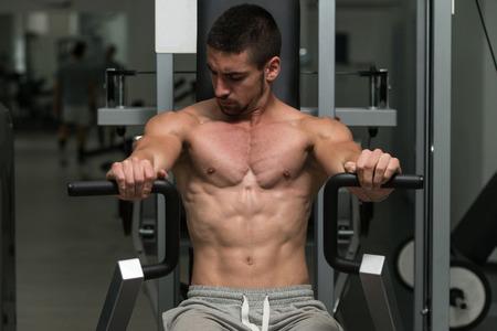 ejercicio aeróbico: Bodybuilder joven que hace ejercicio de peso pesado para el pecho