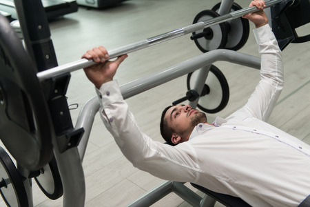 moving activity: Business Man In Gym Exercising Chest On The Bench Press