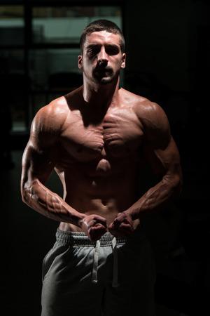 well build: Athlete Muscular Brutal Bodybuilder Emotional Posing In A Dark Gym