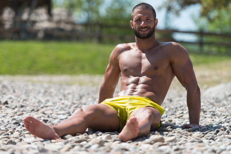nude outdoors: Smiling Handsome Guy Resting On Beach Outdoors