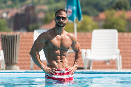 nude body: Fashion Portrait Of A Very Muscular Sexy Man In Underwear At Swimming Pool Stock Photo