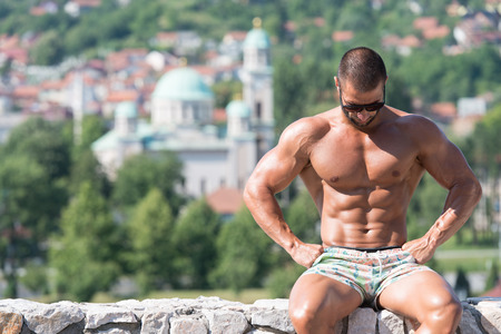 physically fit: Portrait Of A Physically Fit Man Showing His Well Trained Body Outdoors In Summer Time