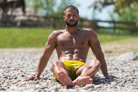 nude male body: Smiling Handsome Guy Resting On Beach Outdoors