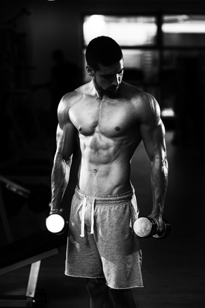 curls: Young Man Working Out Biceps - Dumbbell Concentration Curls Stock Photo