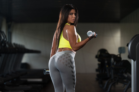 Sexy Latina Woman Working Out Biceps In Fitness Center - Dumbbell Concentration Curls Stock Photo
