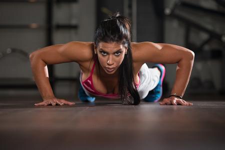 mujer deportista: Joven atleta de la mujer que hace pectorales como parte del entrenamiento de musculación