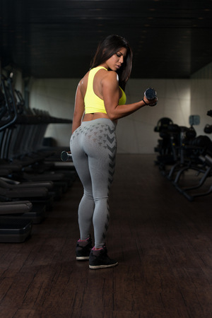 sexy latina: Sexy Latina Woman Working Out Biceps In Fitness Center - Dumbbell Concentration Curls Stock Photo