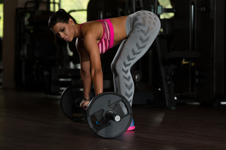latina female: Young Latina Woman Working Out Back With Barbell In Fitness Center