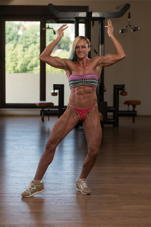 only the biceps: Portrait Of A Middle Aged Woman Posing Bodybuilding Poses In Modern Fitness Center