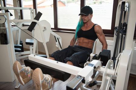 muscle training: Mittlere gealterte Frau tun Bein Übungen Mit Maschine in der Gymnastik Lizenzfreie Bilder