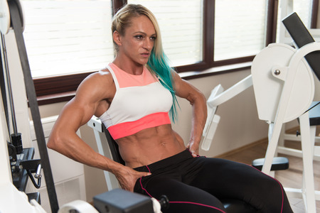 quadriceps: Middle Aged Woman Doing Leg Exercises With Machine In Gym