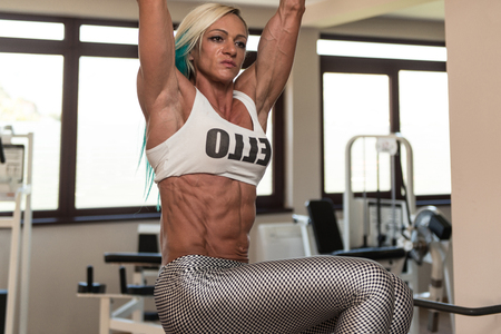 raises: Middle Aged Woman Performing Hanging Leg Raises Exercise - One Of The Most Effective Ab Exercises Stock Photo