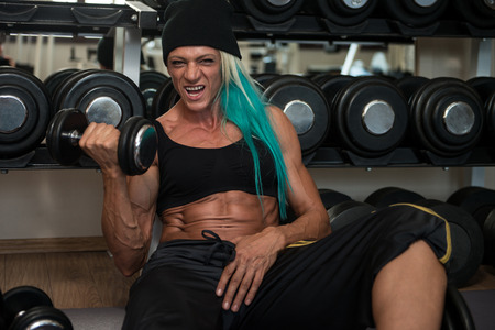 only the biceps: Middle Aged Woman Doing Heavy Weight Exercise For Biceps With Dumbbells In Fitness Center