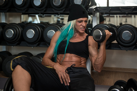 only the biceps: Middle Aged Woman Doing Heavy Weight Exercise For Biceps With Dumbbells In Fitness Centar Stock Photo