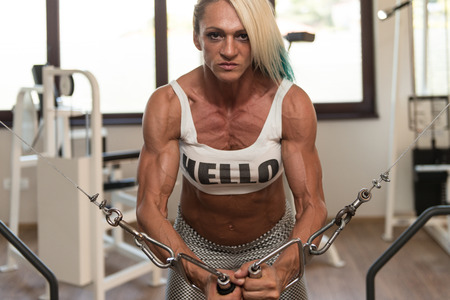 crossover: Mature Woman Is Working On Her Chest With Cable Crossover In A Fitness Center Stock Photo