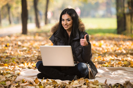 e pretty: Beautiful Woman Working On Laptop In Park During Autumn Season