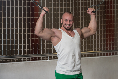 Young Bodybuilder Is Working On His Biceps With Cable Crossover In Gym