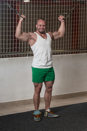 crossover: Young Bodybuilder Is Working On His Biceps With Cable Crossover In Gym
