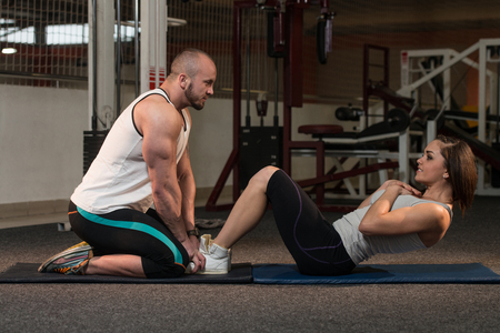 Young Couple Doing Sit Ups As Part Of Bodybuilding Training In The Gym
