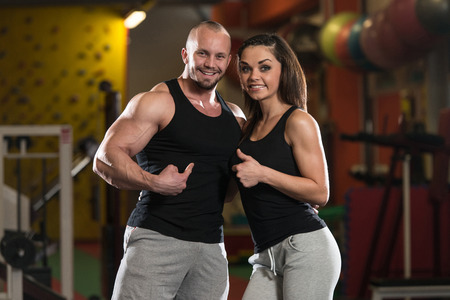 Portrait Of A Sexy Couple In The Gym With Exercise Equipment Showing Thumbs Up