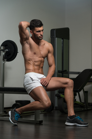 physically fit: Portrait Of A Young Physically Fit Man Resting On Bench And Showing His Well Trained Body Stock Photo