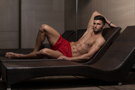 swimsuit: Young Man Resting On Sun Loungers By Swimming Pool And Flexing Muscles