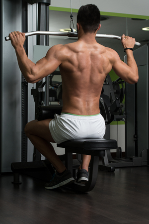 heavy weight: Arabic Bodybuilder Doing Heavy Weight Exercise For Back On Machine Stock Photo