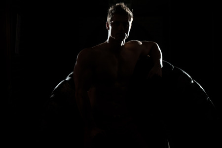 siluet: Siluet Portrait Of Muscular Young Man With Tire