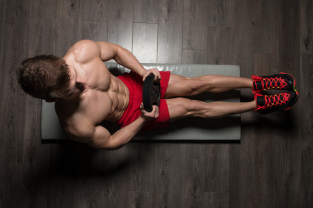 laying abs exercise: Healthy Young Man Exercising Abdominals On Foor With Weights
