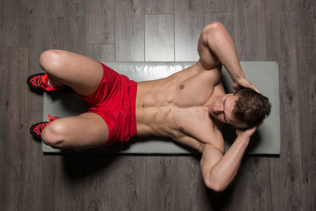laying abs exercise: Young Healthy Man Exercising Abdominals On Foor
