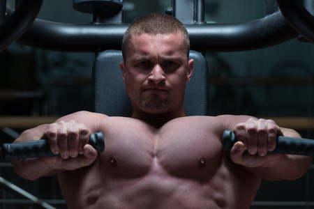 well build: Bodybuilder Doing Heavy Weight Exercise For Chest On Machine