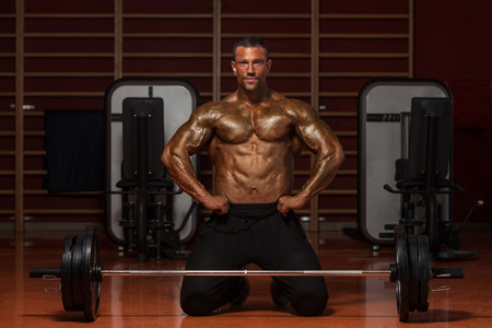 flexing: Serious Man Standing Strong In The Gym And Flexing Muscles