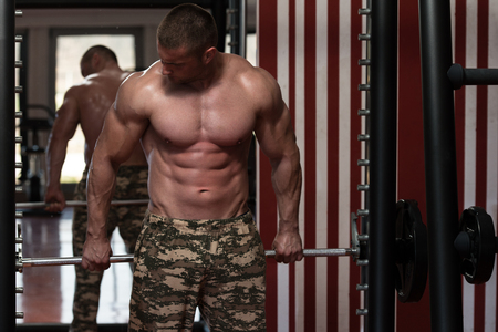 trapezius: Male Bodybuilder Doing Heavy Weight Exercise For Trapezius