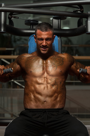 well build: Adult Bodybuilder Doing Heavy Weight Exercise For Chest On Machine