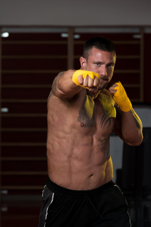 combative sport: Muscular Boxer MMA Fighter Practice His Skills Stock Photo