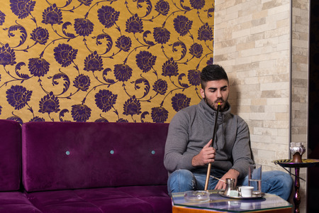 turkish ethnicity: Man Smoking Turkish Hookah In The Cafe With Colorful Walls On Background