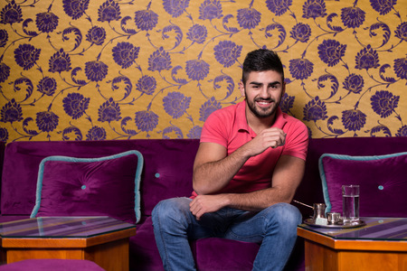 turkish ethnicity: Young Man Drinking Coffee In The Cafe Bar With Colorful Walls On Background