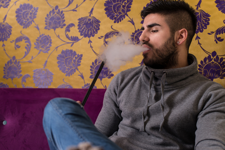 european ethnicity: Man Smoking Turkish Hookah In The Cafe With Colorful Walls On Background