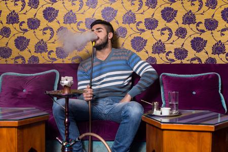 east espresso: Young Man Smoking Shisha At Arabic Restaurant - Man Exhaling Smoke Inhaling From A Hookah