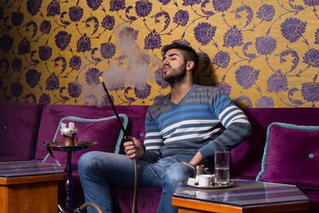 hombre fumando: Hombre fumar narguile turco en la cafetería con las paredes de colores en fondo