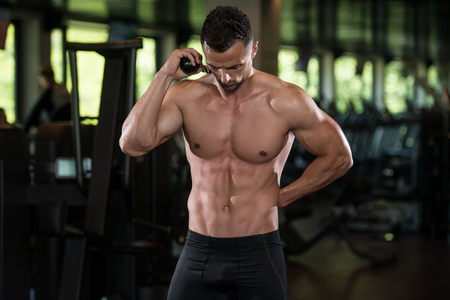 physically fit: Portrait Of A Physically Fit Man Posing With Triceps Rope In Modern Fitness Center Gym