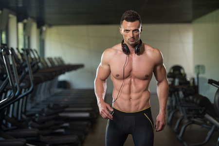 physically fit: Portrait Of A Physically Fit Man Posing In Modern Fitness Center Gym