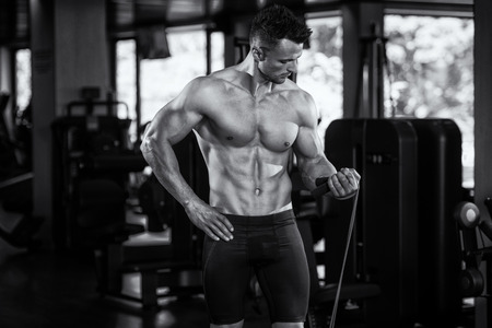physically fit: Portrait Of A Physically Fit Man Posing With Jumping Rope In Modern Fitness Center Gym