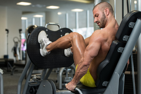 quadriceps: Attractive Young Man Doing Leg Press On Machine In Gym Stock Photo
