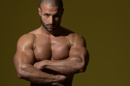 physically fit: Portrait Of A Physically Fit Man Showing His Well Trained Body In Dark Room