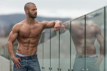 physically fit: Portrait Of A Physically Fit Young Man Posing Outdoors