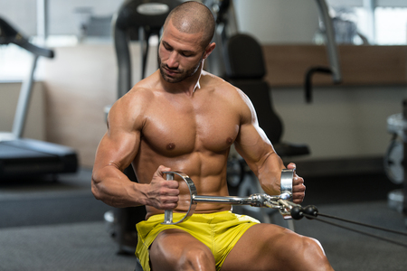 heavy weight: Young Bodybuilder Doing Heavy Weight Exercise For Back On Machine Stock Photo