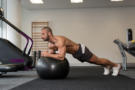 Young Man Exercising Abs On Ball Workout Posture In Fitness Club